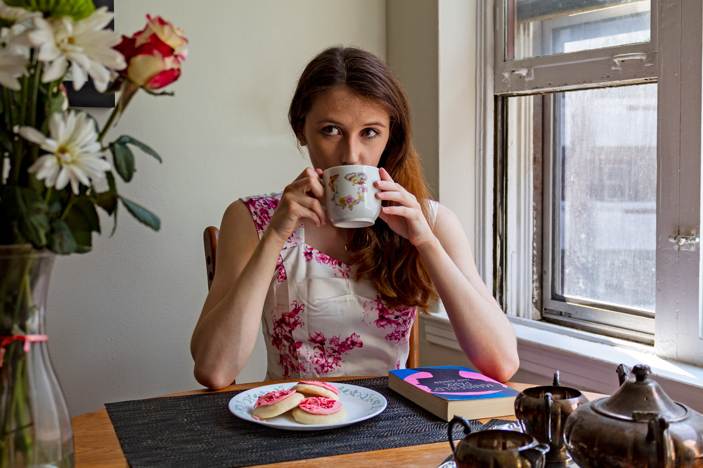 Woman sipping on a cup of tea; in front of her are cookies and a book