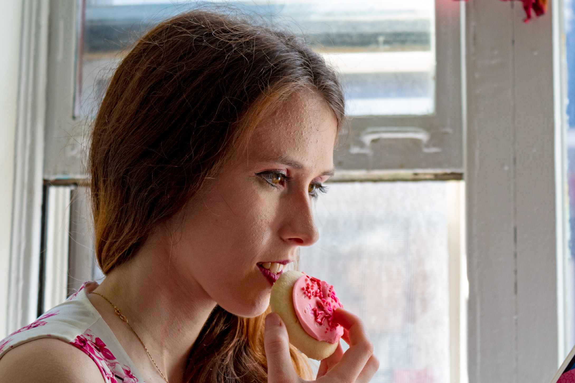 Woman holding a sugar cookie with pink frosting near her mouth