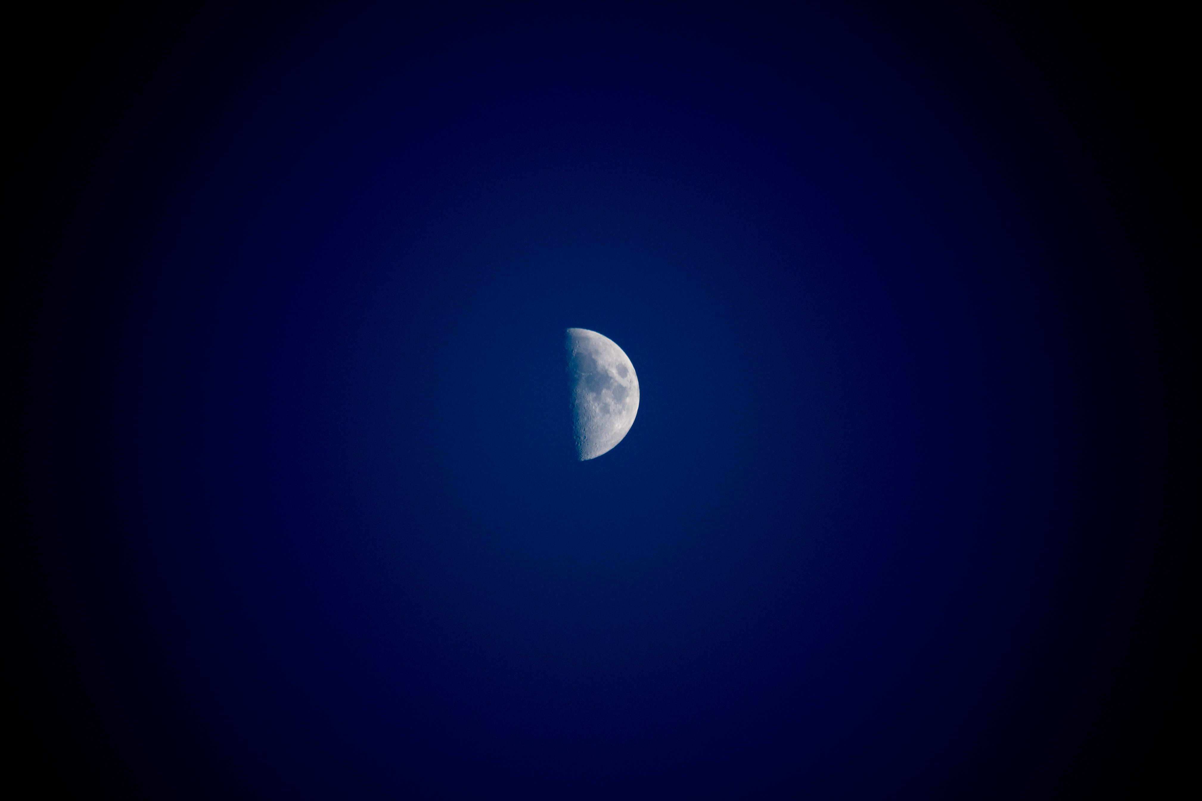 Pale half-moon against a blue background with strong vignetting