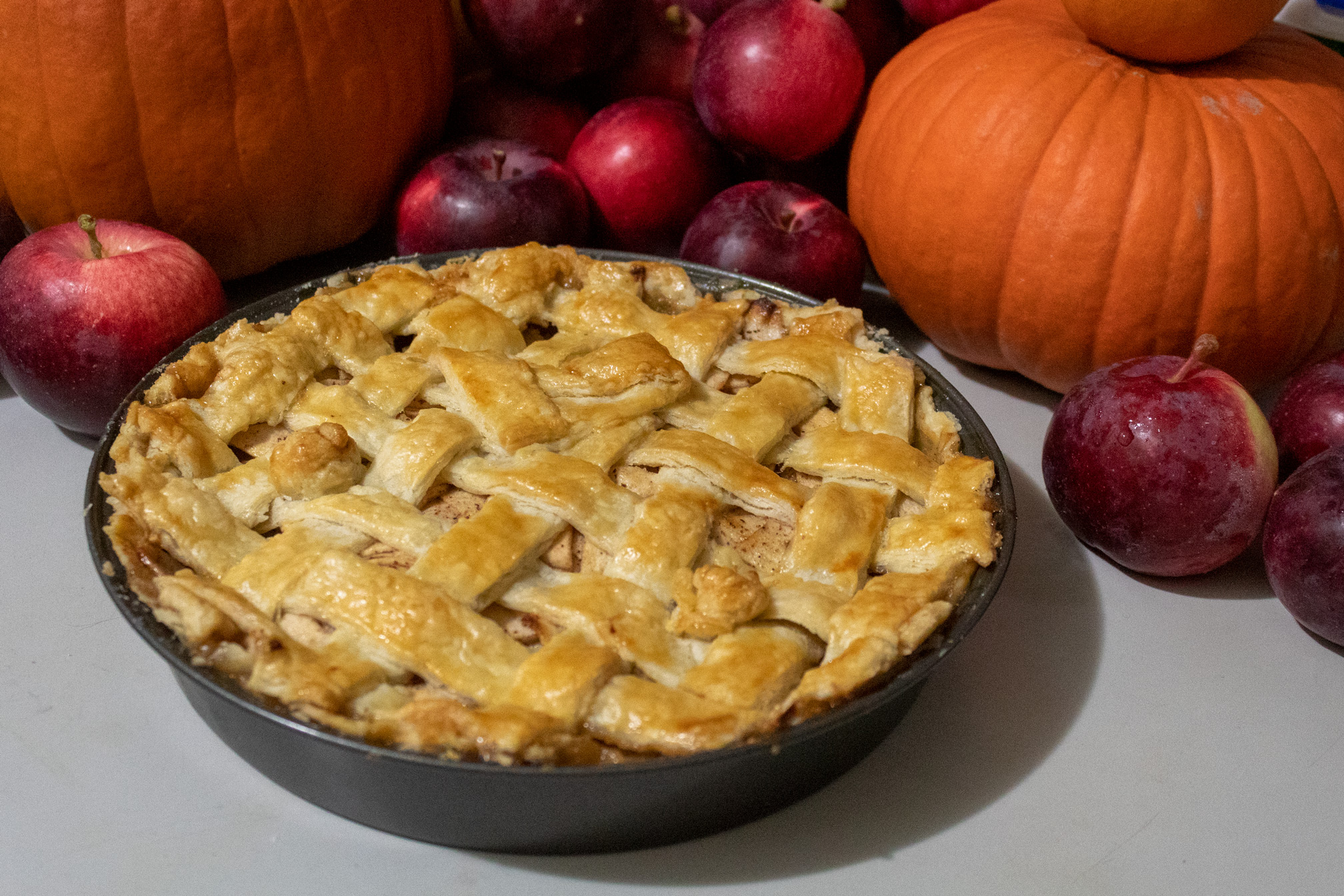 Apple pie with latticed top crust viewed from a skewed angle against a backdrop of Spartan apples and pumpkins
